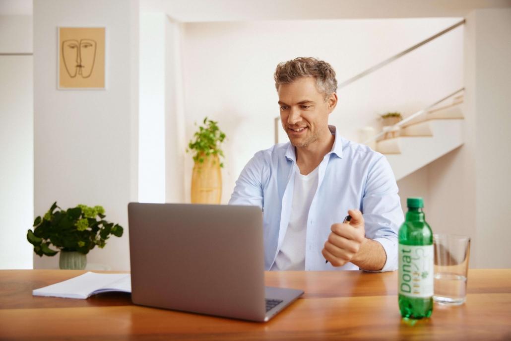 Moški sedi za računalnikom in pije Donat.