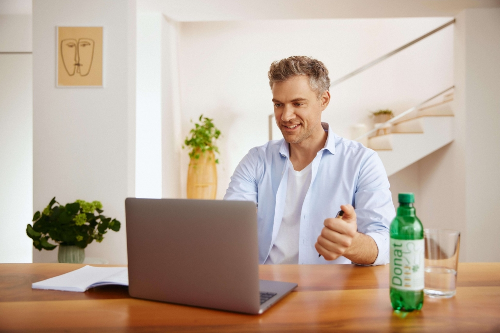 The man sits at the computer and drinks Donat.